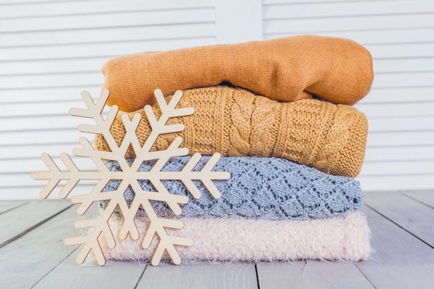 Pila de suéteres de punto blanco acogedor en una mesa de madera