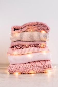 Pila de suéteres de punto con guirnalda en el piso.