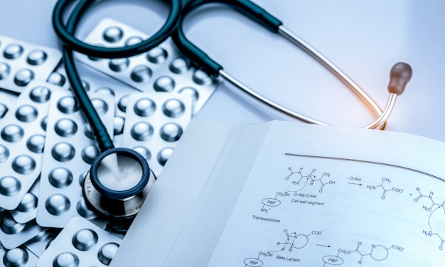 Pila de tabletas píldora en blister con libro de estructura de drogas y estetoscopio. equipamiento médico para diagnóstico. libro de texto de farmacología.