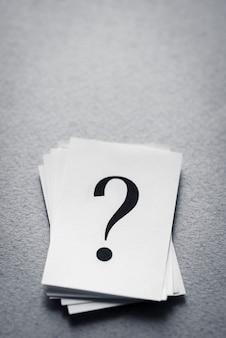 Pila de tarjetas de papel con un signo de interrogación impreso