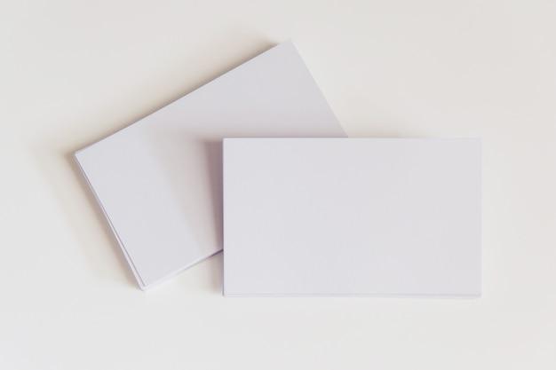 Pila de tarjetas de visita blancas en blanco. tarjetas de visita de la maqueta en el fondo blanco con el camino de recortes