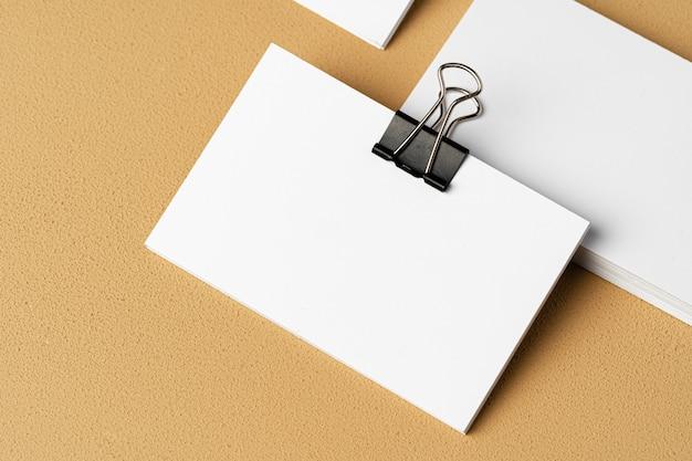 Pila de tarjetas de visita blancas con un clip sobre fondo beige