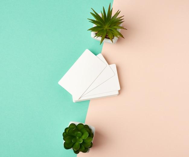 Pila de tarjetas de visita en blanco blancas rectangulares sobre un fondo beige verde