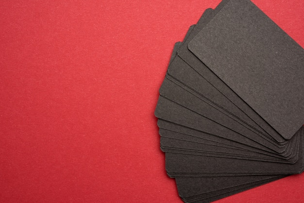 Pila de tarjetas de visita en blanco de papel negro rectangular sobre fondo rojo