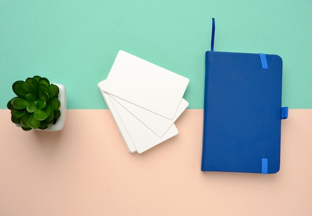 Pila de tarjetas de visita en blanco rectangulares en blanco y cuaderno azul en un espacio verde beige