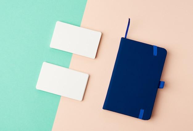Pila de tarjetas de visita en blanco rectangulares en blanco y cuaderno azul sobre un fondo verde beige