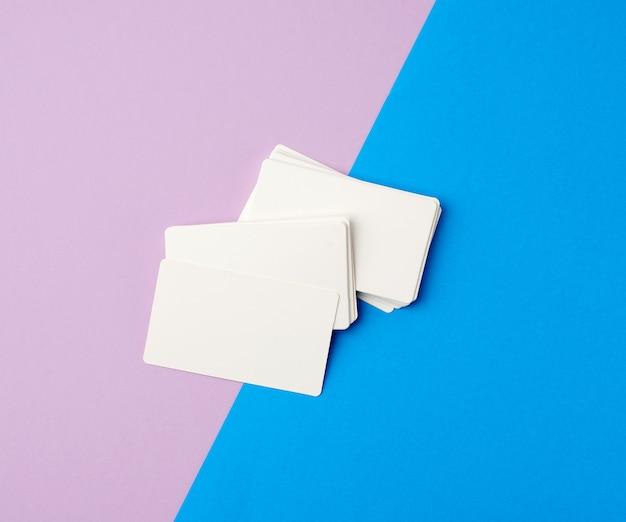 Pila de tarjetas de visita en blanco rectangulares en blanco sobre un fondo azul