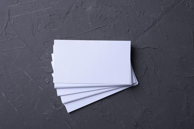 Pila de tarjetas de visita en blanco sobre una superficie oscura