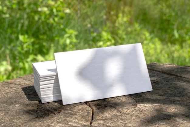 Pila de tarjetas de visita tipográficas en blanco acostado en un tocón escenario al aire libre con sombras florales