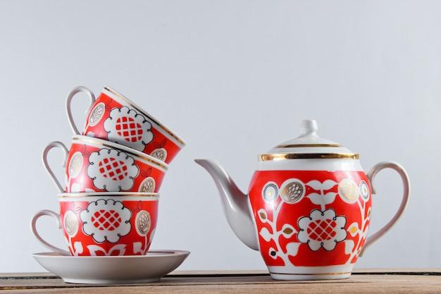 Pila de tazas de cerámica antiguas y una tetera en la mesa de madera contra una pared blanca