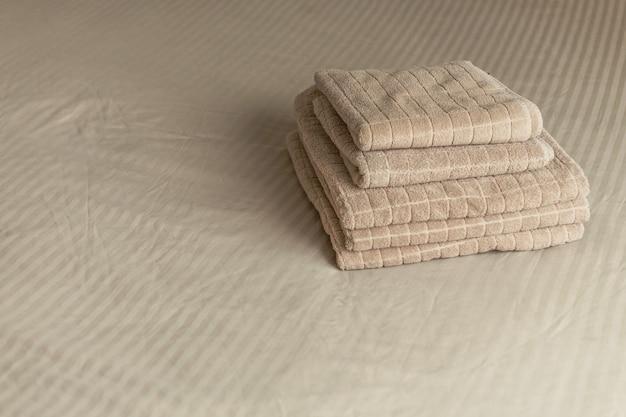 Pila de toalla beige del hotel en cama en interior del dormitorio. tonificacion vintage
