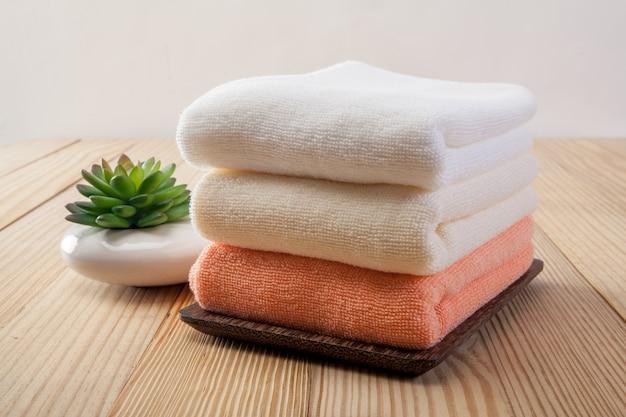 Pila de toallas de baño con flores de lavanda en luz de fondo de madera closeup