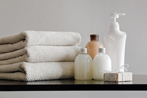 Pila de toallas, botellas con champú, loción corporal, leche de ducha y jabón hecho a mano sobre fondo neutro.