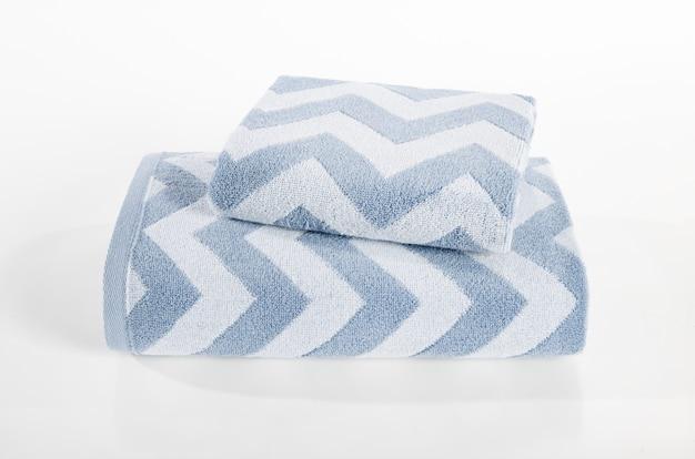 Pila de toallas de felpa, toallas en la pila contra el fondo blanco, pila de toallas azules y blancas