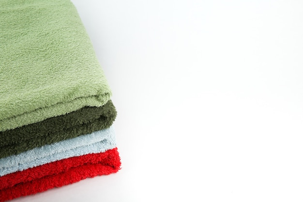 Pila de toallas limpias dobladas sobre fondo blanco con espacio de copia