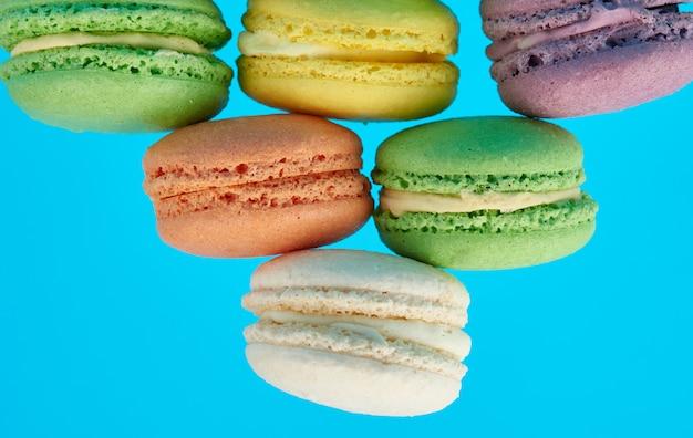Pila de tortas de macarons al horno redondas multicolores en un espacio azul