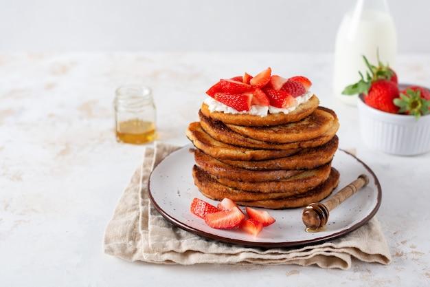 Pila de tostadas francesas con requesón, miel y fresas para el desayuno