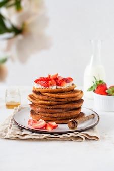 Pila de tostadas francesas con requesón, miel y fresas para el desayuno.