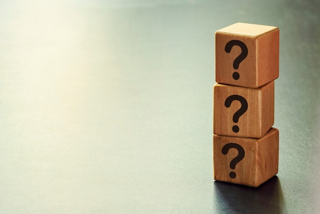 Pila de tres cubos de madera con signos de interrogación.