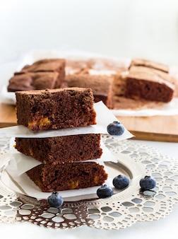 Pila de tres piezas cuadradas de brownies de chocolate caseras y arándanos.