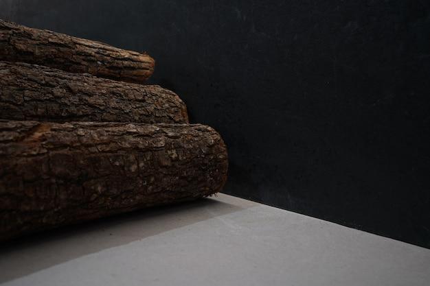 Pila de troncos de madera sobre una superficie gris y un fondo oscuro