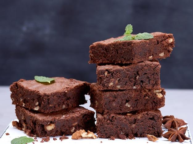 Pila de trozos cuadrados horneados de pastel de brownie de chocolate con nueces