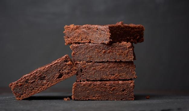 Pila de trozos cuadrados de pastel de chocolate brownie sobre un fondo negro