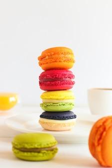 Pila de varios macarrones sobre la mesa con tazas de jugo de naranja y café postre francés