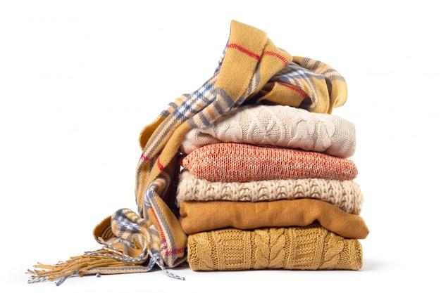 Pila de varios suéteres y una bufanda.