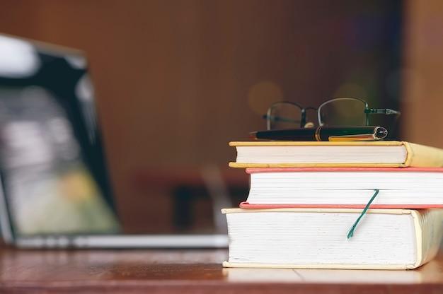 Pila de viejos abucheos en la mesa de madera con el portátil en la biblioteca.