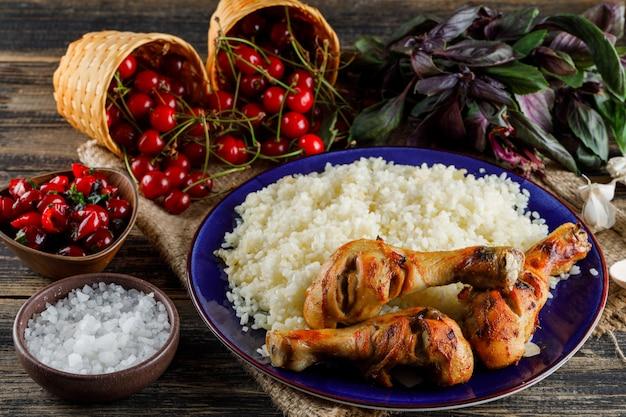 Pilaf con carne de pollo, cereza, sal, albahaca, ajo en un plato sobre madera y pedazo de saco alto.