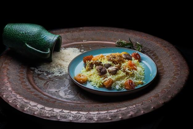 Pilaf con frutos secos y secos y castañas y jarra en plato redondo