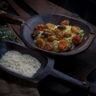 Pilaf con frutos secos y secos y hojas de castaño y arroz y romero en placa de madera