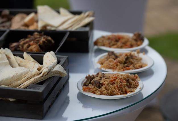 Pilaf listo y servido. plato nacional de cocina oriental. lavash, panecillos y pan. comidas listas.
