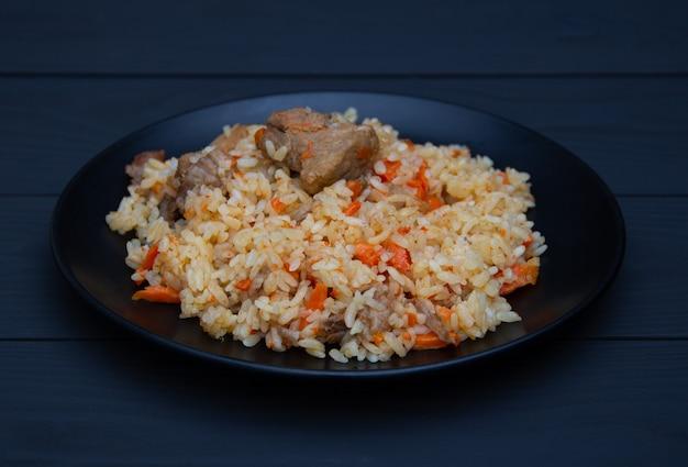 Pilaf sabroso tradicional con ajo y especias en placa negra. plato nacional de uzbekistán.