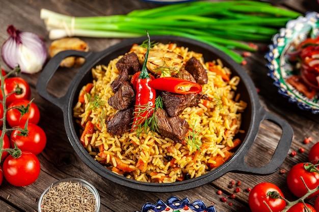 Pilaf uzbeco nacional con carne en una sartén de hierro fundido, sobre una mesa de madera.