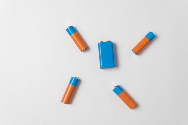 Pilas aa y pp3 sobre fondo blanco. baterías de diferentes tipos. vista superior