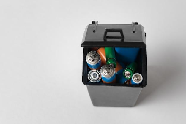 Pilas alcalinas en contenedor de basura negro sobre fondo blanco. concepto de reciclaje de baterías
