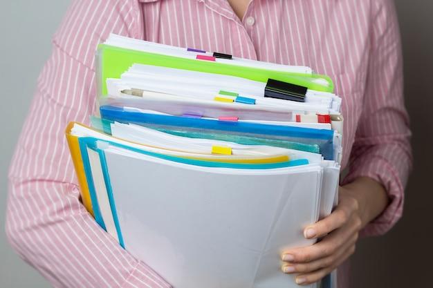 Pilas de documentos en archivos de papel en manos, documentos de informes de negocios.