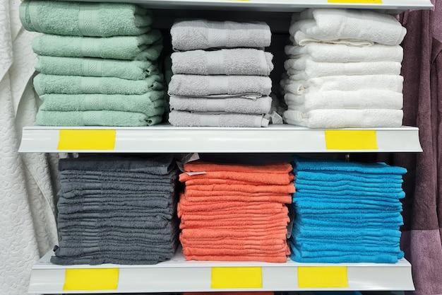 Pilas de hermosas toallas blancas, marrones, azules, verdes y grises de colores pastel se venden en una vitrina en la tienda. espacios en blanco amarillos vacíos para los precios. estilo escandinavo, lagom.