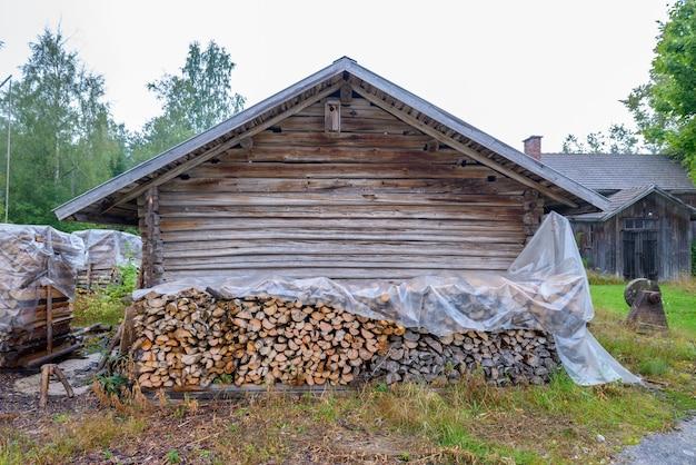 Pilas de leña picada junto a la antigua casa de madera