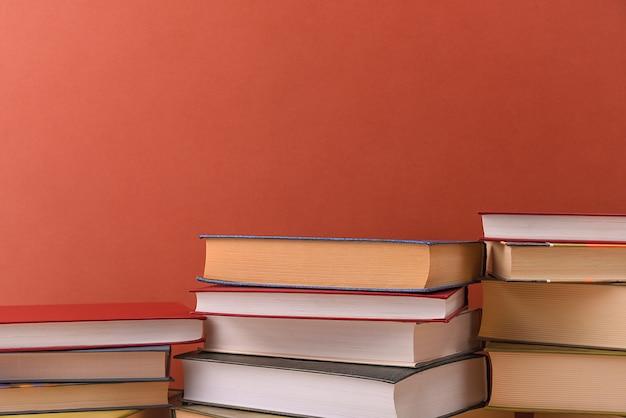 Pilas de libros varios en un primer plano de fondo marrón. regreso a la escuela, educación, aprendizaje,