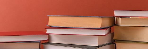 Pilas de libros varios sobre un primer plano de fondo marrón. libros de tapa dura en diferentes colores.