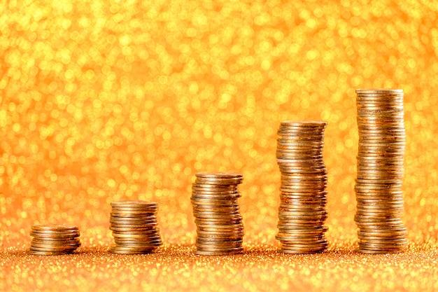 Pilas de monedas de cobre sobre fondo dorado