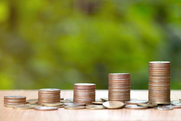 Pilas de monedas en la mesa de madera