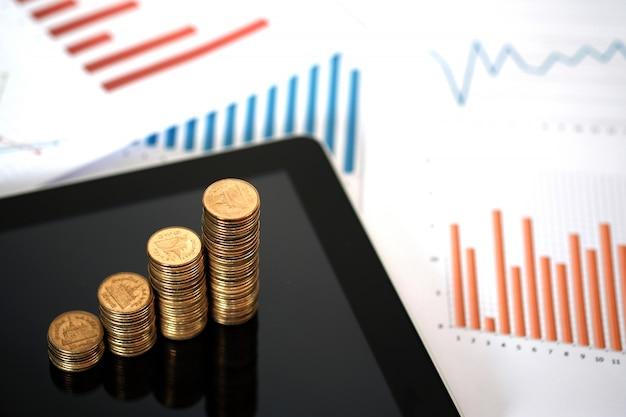 Pilas de monedas en una tableta con gráficos