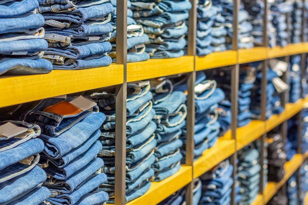 Pilas ordenadas de jeans doblados en los estantes de las tiendas