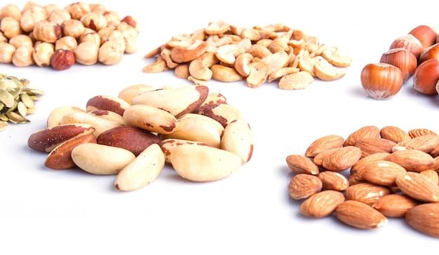 Pilas de varios frutos secos y semillas aislados en blanco
