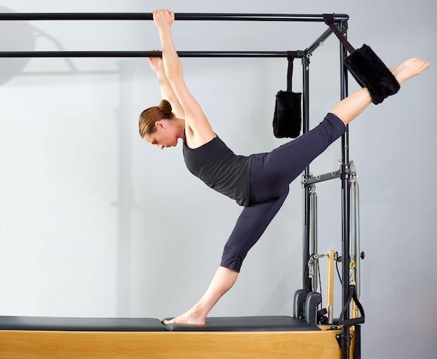 Pilates mujer en cadillac piernas abiertas estiramiento ejercicio