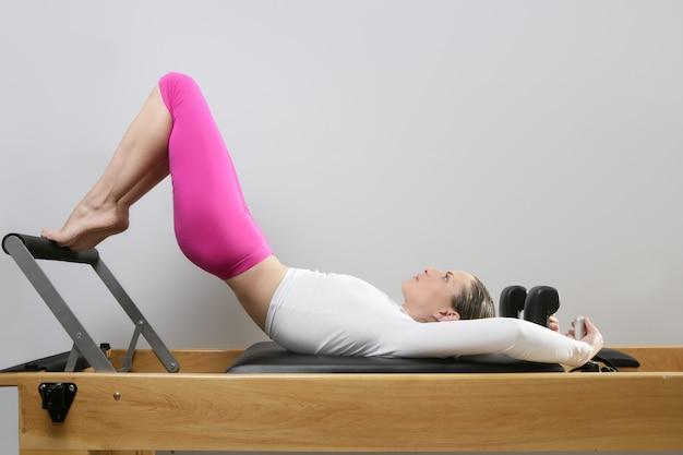 Pilates reformer mujer gimnasio fitness profesor piernas